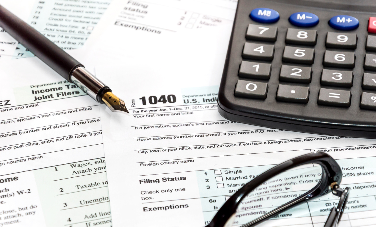 Pen, glasses and calculator on tax form 1040. business concept.